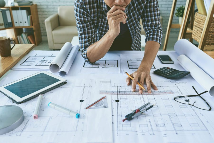 Cropped image of architect working with construction plans